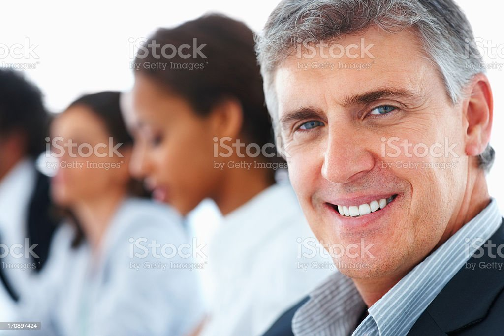 Closeup of a handsome business man with other colleagues at the back stock photo