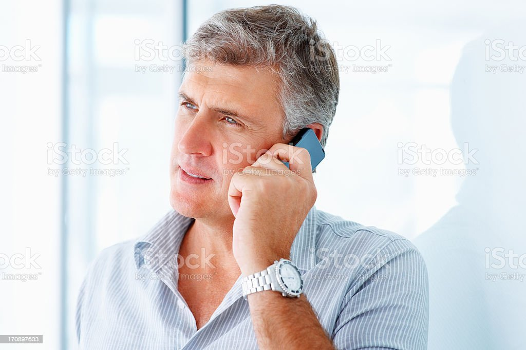Closeup of a handsome mature man speaking on a cellphone stock photo