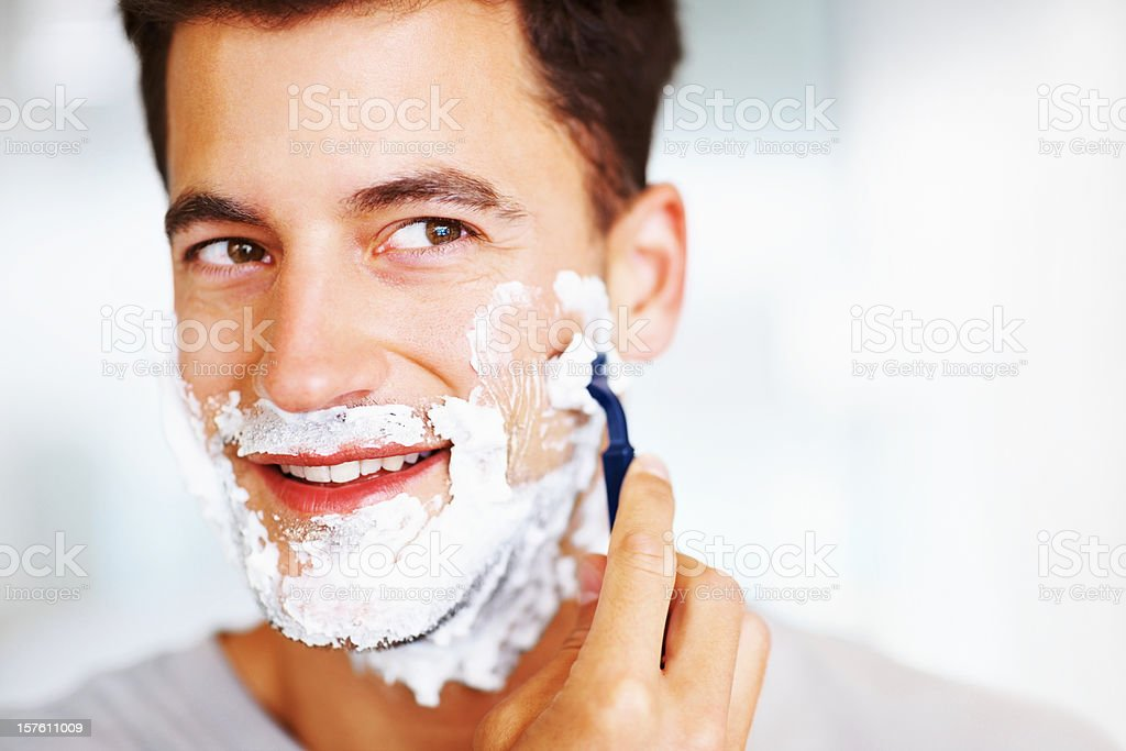Close-up of a handsome smiling man shaving royalty-free stock photo
