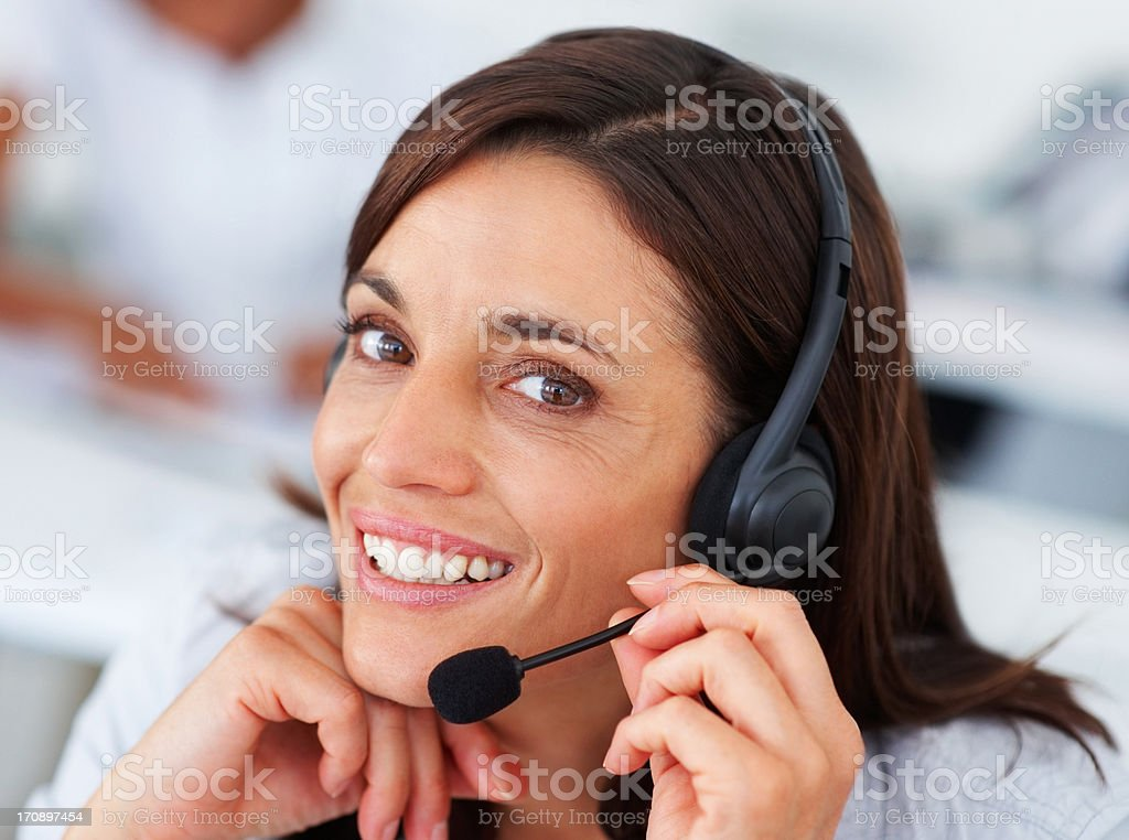 Closeup of a happy beautiful operator wearing a working on a headphone royalty-free stock photo