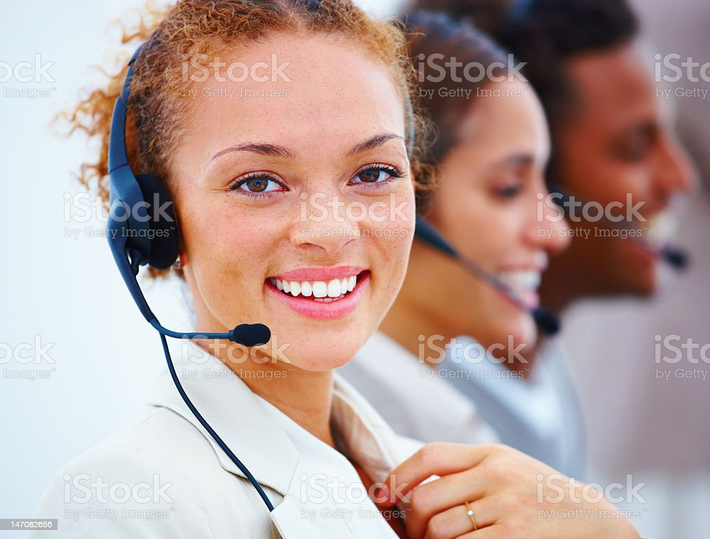 Close-up of a happy pretty executive with headset royalty-free stock photo