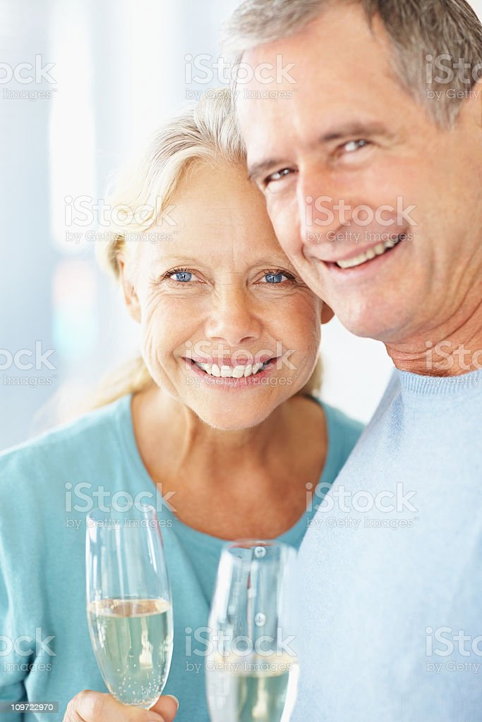 Closeup of a happy retired couple holding champagne glasses royalty-free stock photo