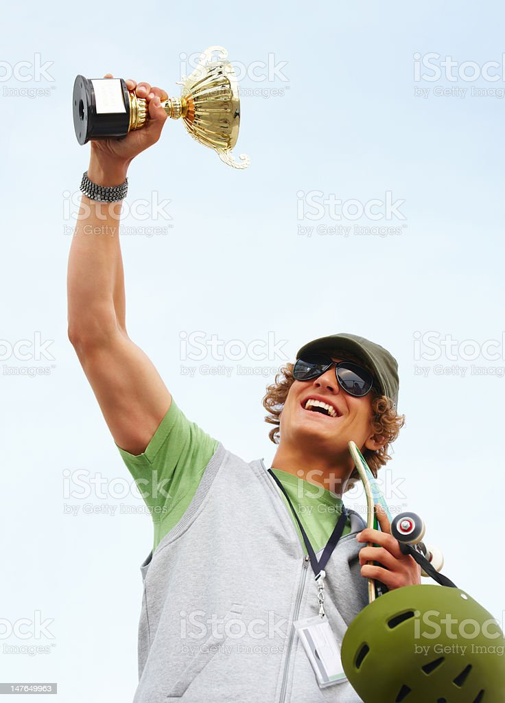 Close-up of a happy teenage boy holding cup against sky royalty-free stock photo