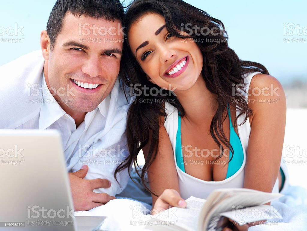 Close-up of a happy young couple lying together on beach royalty-free stock photo