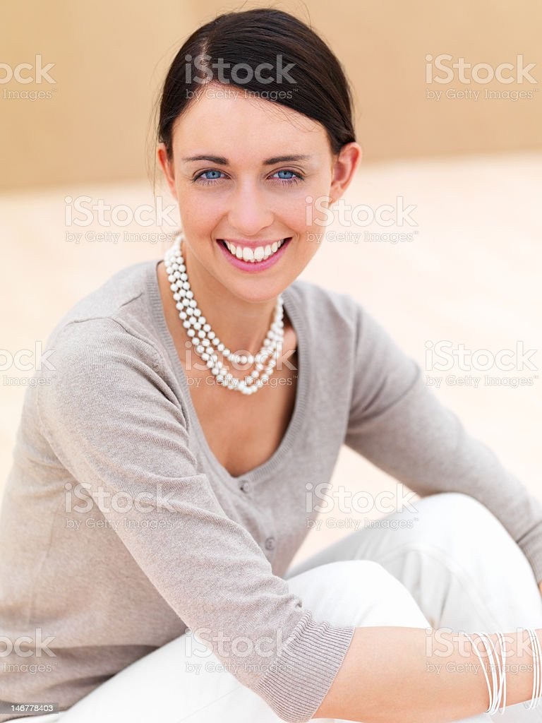 Close-up of a happy young woman sitting on floor stock photo