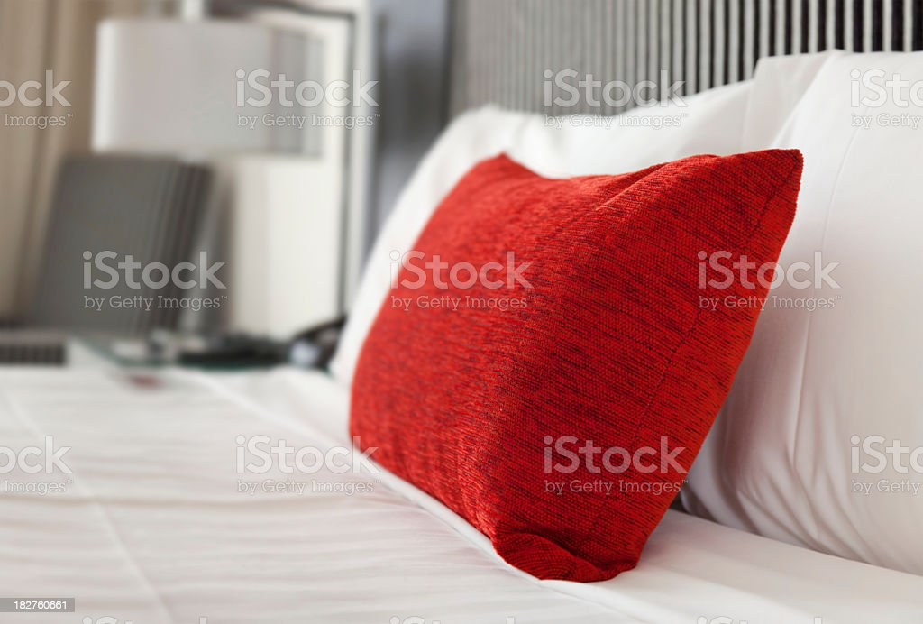 Close-up of a hotel bed with white sheets and one red pillow stock photo