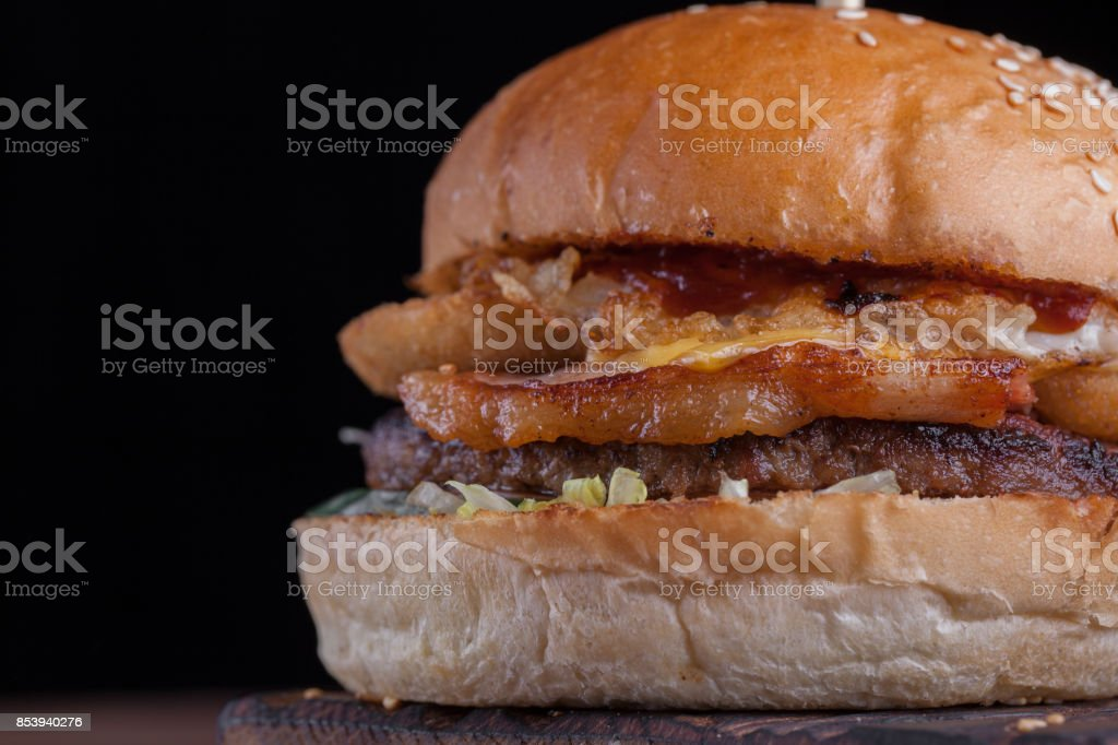 Closeup of a juicy Burger with bacon, fried onion rings and cheese on dark wooden background. stock photo