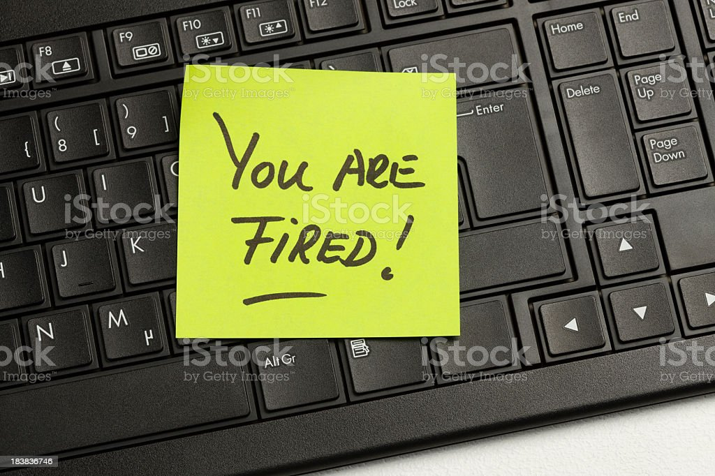 A close-up of a keyboard with a note saying you are fired stock photo