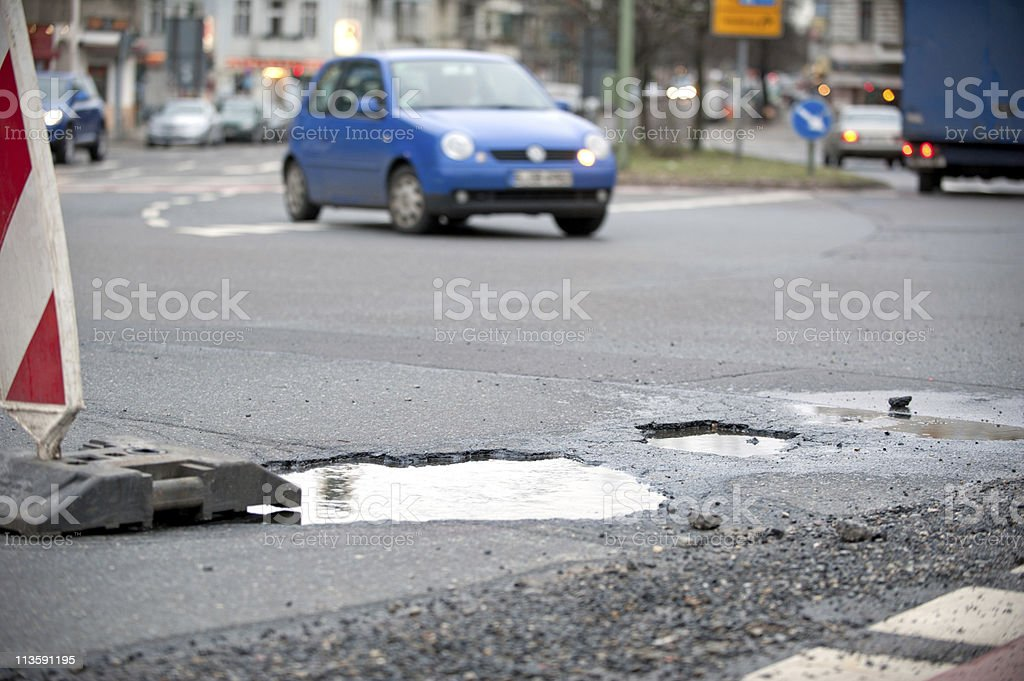 A closeup of a large pothole on a busy street stock photo
