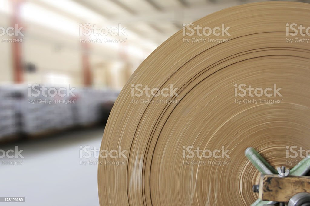 Close-up of a large roll of brown paper in a warehouse stock photo
