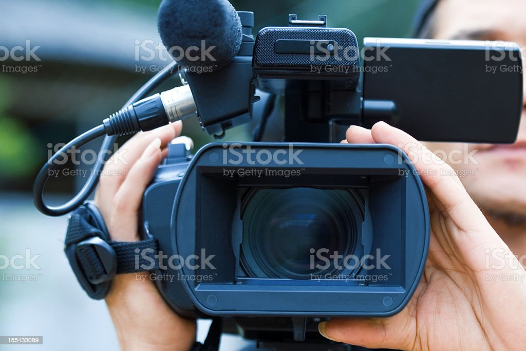 Close-up of a male videographers black camera royalty-free stock photo