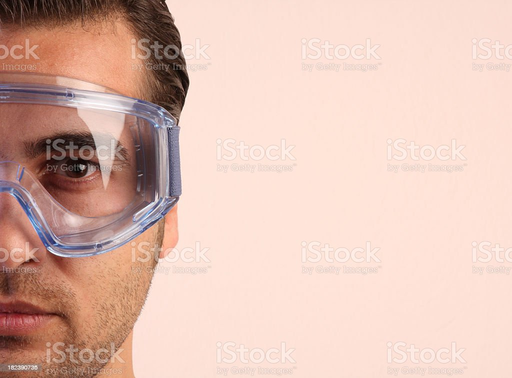 A close-up of a male worker wearing safety glasses royalty-free stock photo