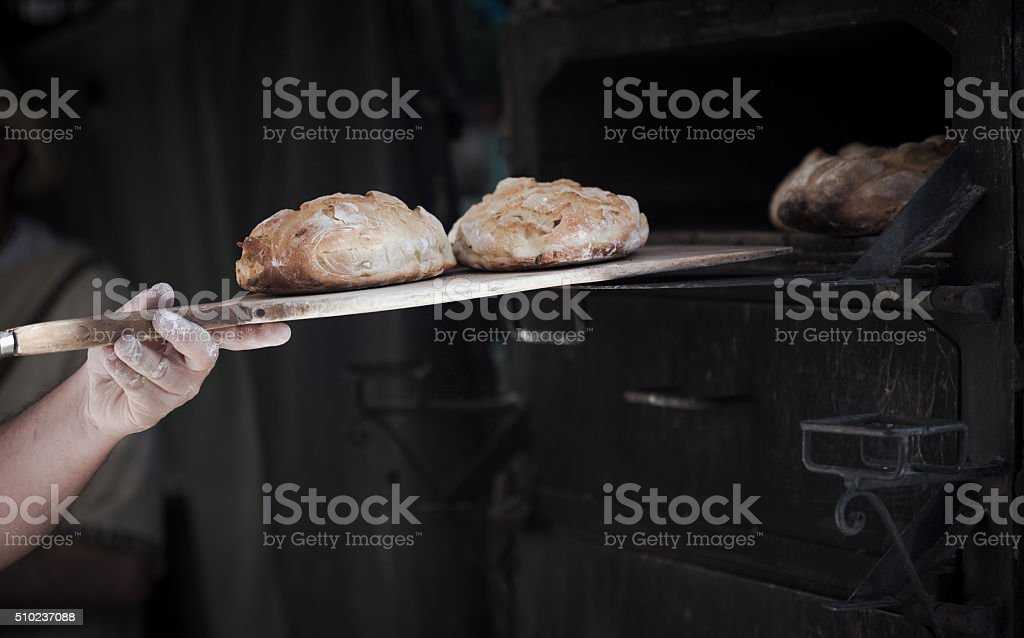 Close-up of a man baker introducing breads in classic oven stock photo