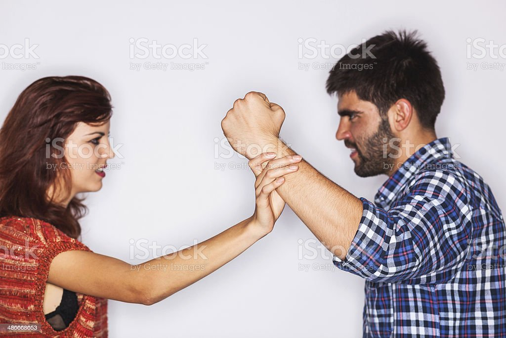 Closeup of a man fist held back by his girlfriend stock photo