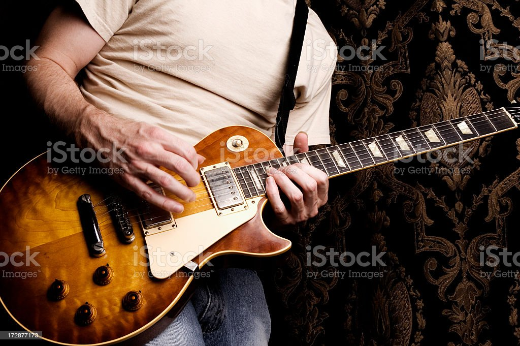 A closeup of a man from the shoulders down playing guitar royalty-free stock photo