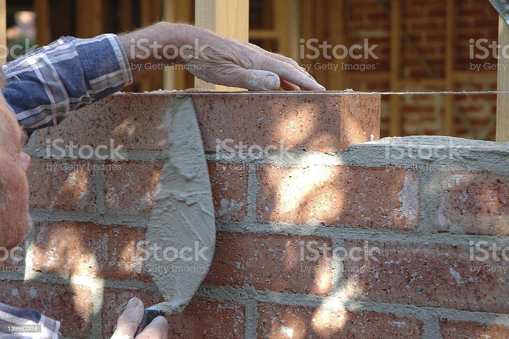 A close-up of a man laying bricks stock photo