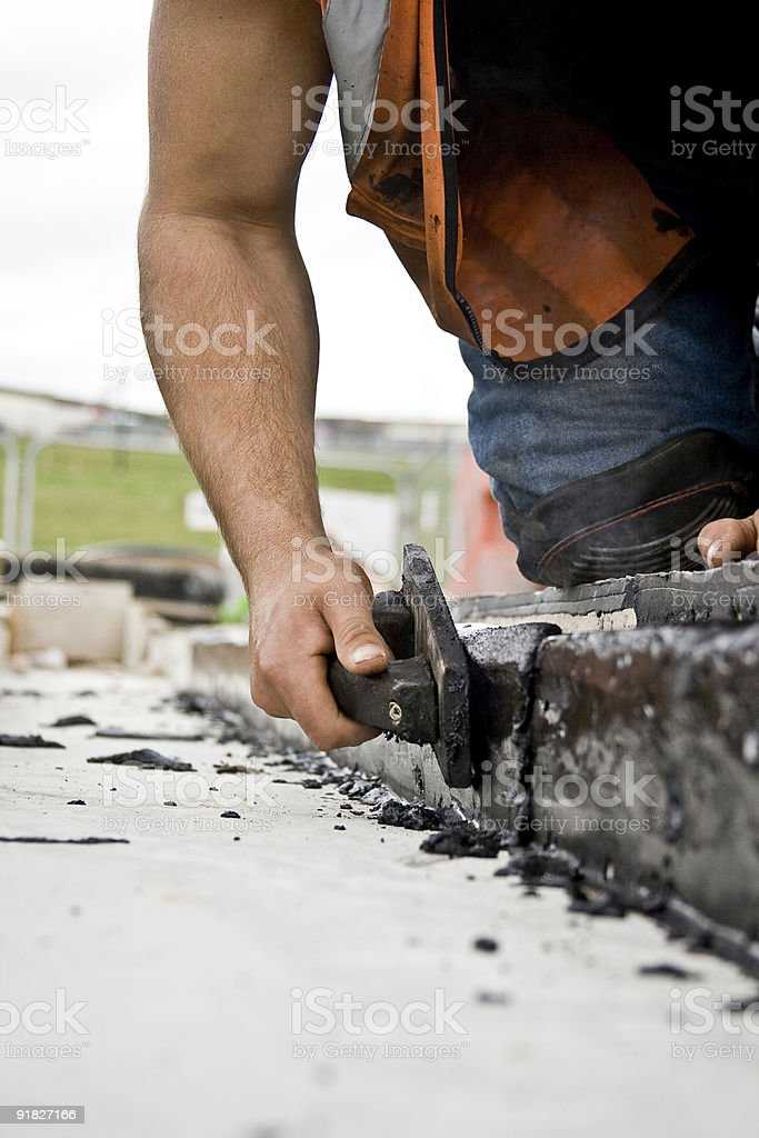 Close-up of a man laying rubber tar stock photo
