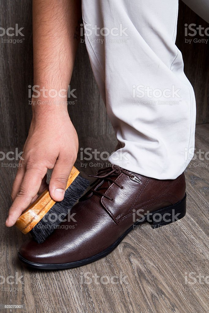 Close-up of a man polishing his brown leather dress shoes stock photo
