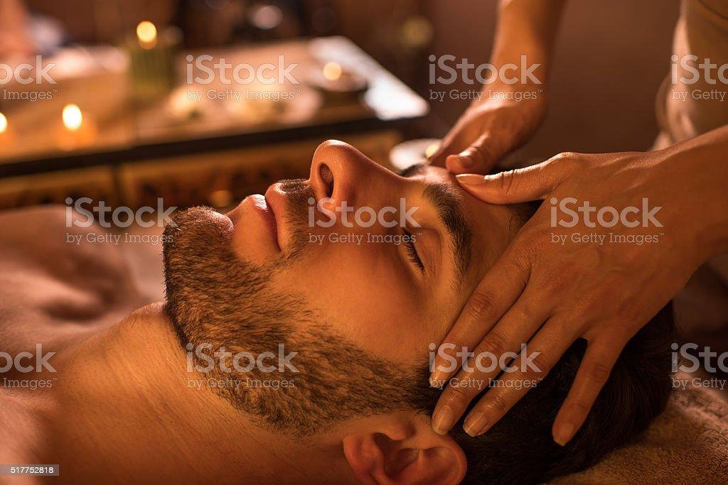 Close-up of a man receiving facial massage at the spa. stock photo
