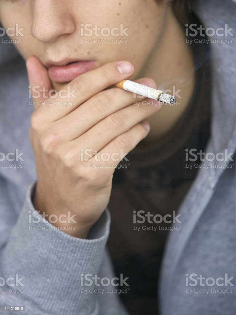 Close-up of a man smoking a cigarette and thinking royalty-free stock photo