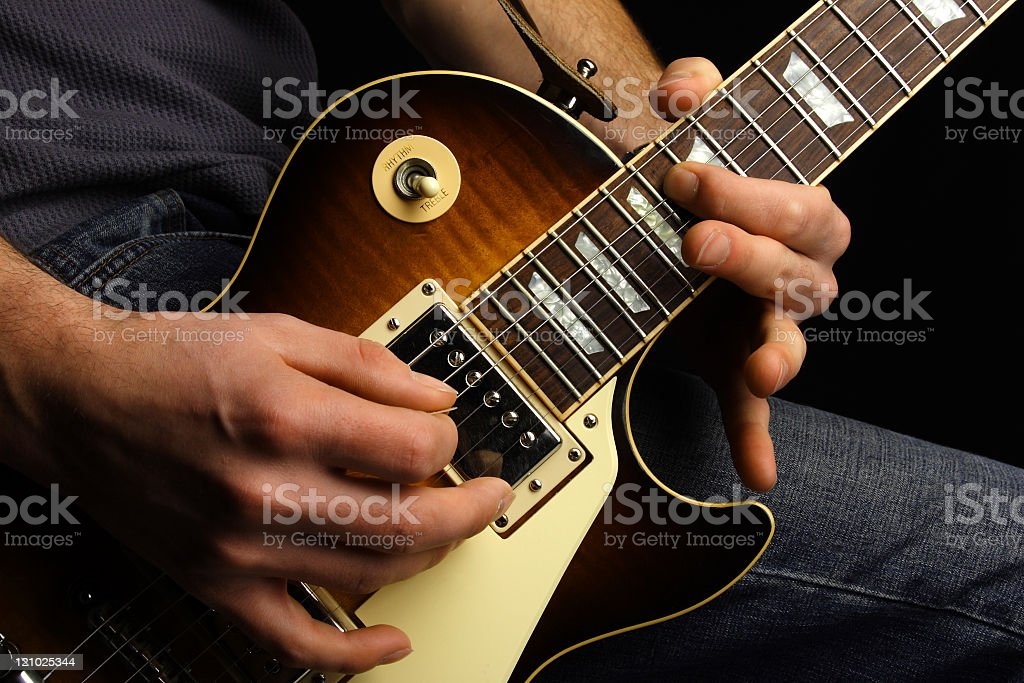 Close-up of a man's hand playing a brown electric guitar stock photo