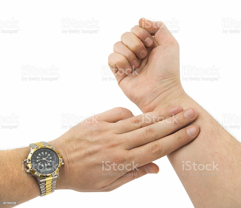 Close-up of a mans hands with a watch taking his pulse royalty-free stock photo