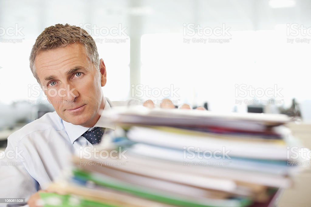 Close-up of a mature businessman with heap of papers royalty-free stock photo