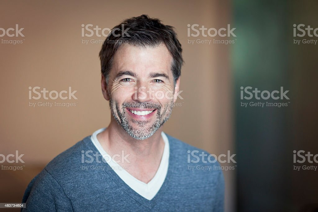 Close-up of a mature man smiling at home stock photo