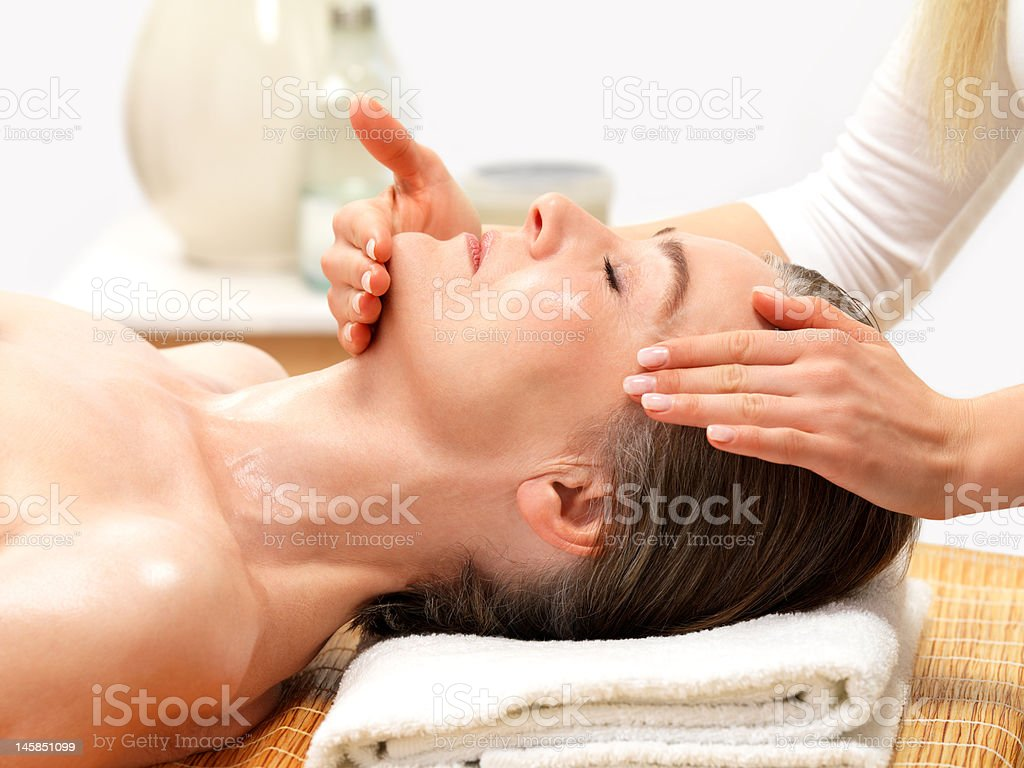 Close-up of a mature woman receiving facial massage royalty-free stock photo