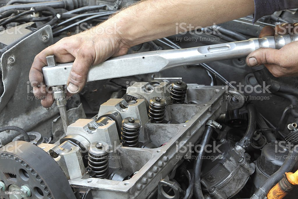 A closeup of a mechanic working on a Diesel engine stock photo