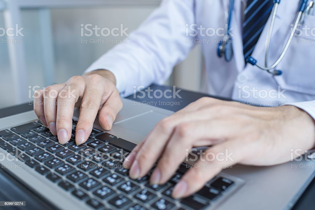 Close-up of a medical worker typing on laptop stock photo
