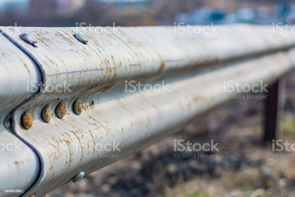 Close-up of a metal highway fence near a old city road stock photo