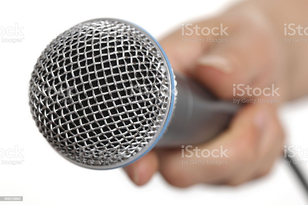 Close-up of a microphone being held by a blurred hand stock photo