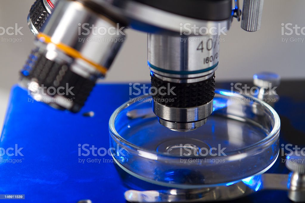 Close-up of a microscope lens on a metallic blue table royalty-free stock photo