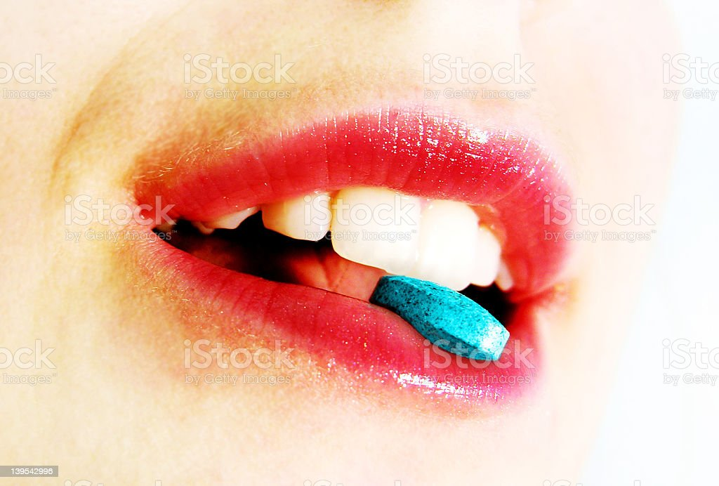 A close-up of a mouth holding q blue pill stock photo