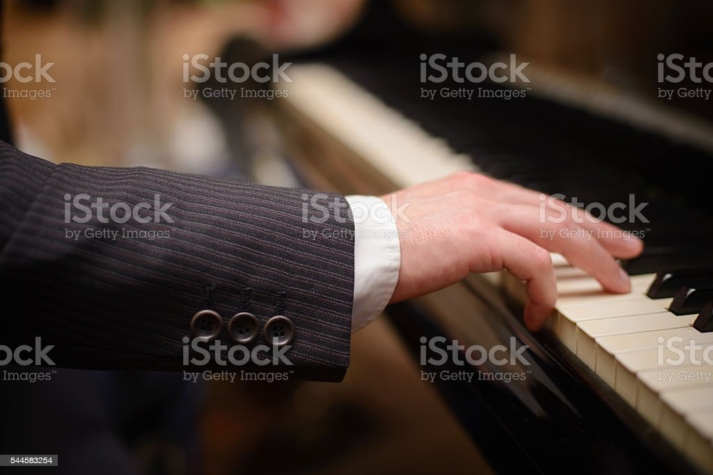 Close-up of a music performer's hand playing the piano stock photo