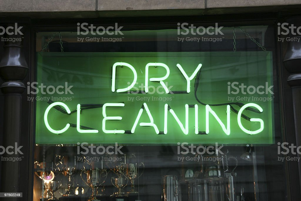 Close-up of a neon green dry cleaning sign in a window stock photo
