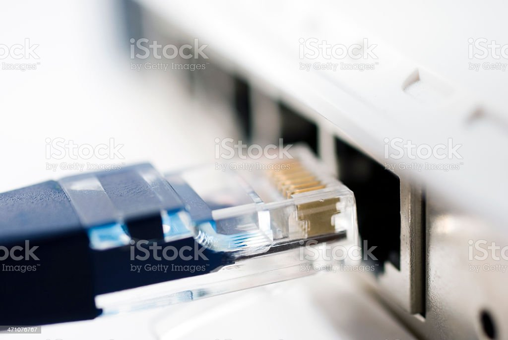 Close-up of a network cable being plugged into a router stock photo