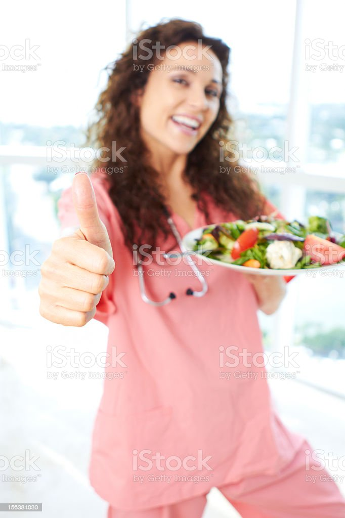 Close-up of a nurse holding salad giving thumbs up stock photo