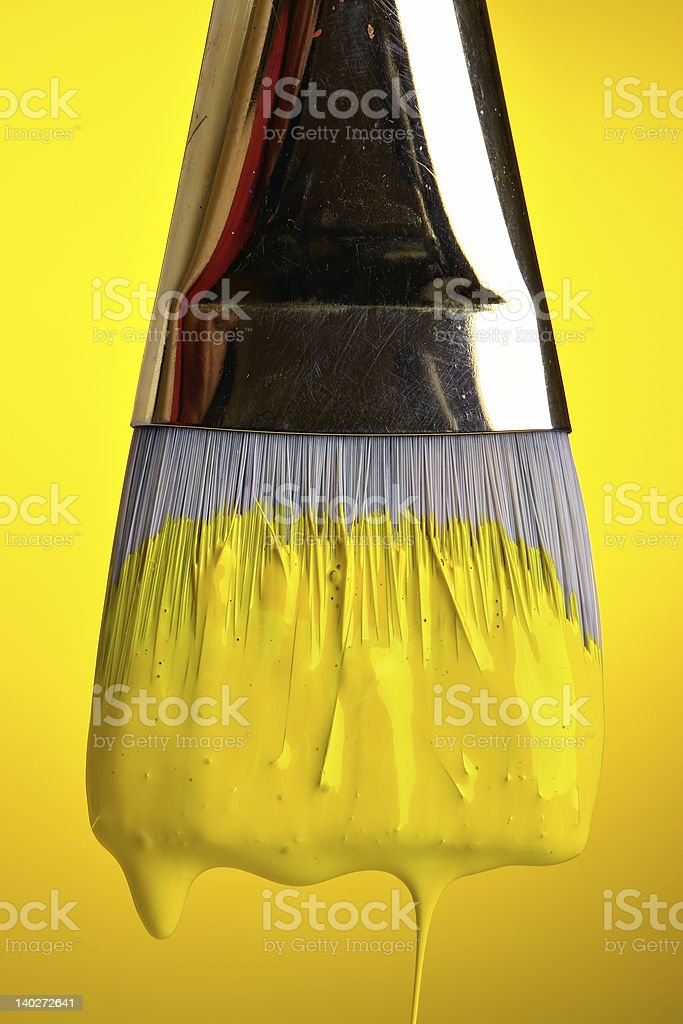 Close-up of a paint brush covered in bright yellow paint royalty-free stock photo