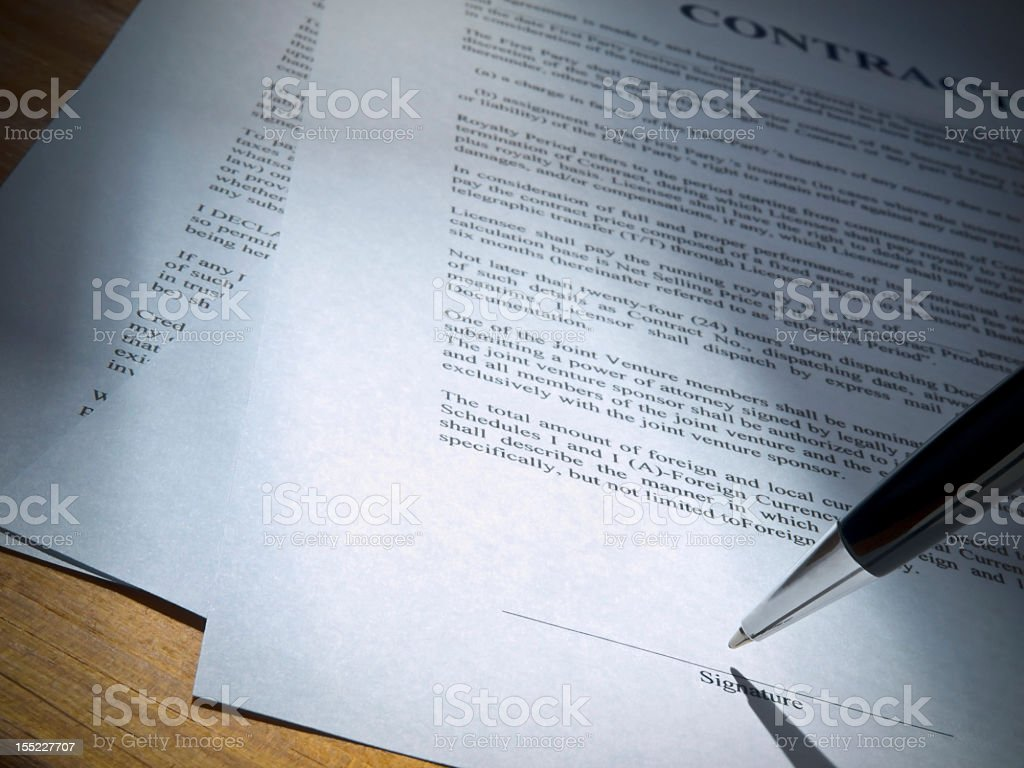 Close-up of a pen over the signature line of a document royalty-free stock photo