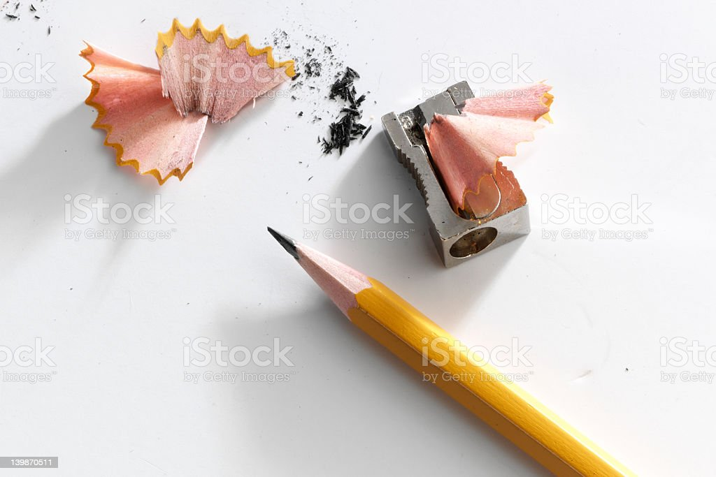 Close-up of a pencil and a sharpener with pencil shavings stock photo