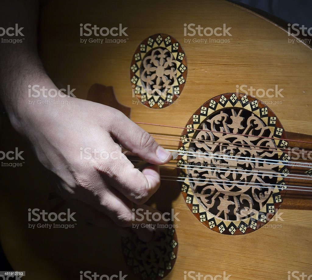 Close-up of a person's hand playing an OUD stock photo