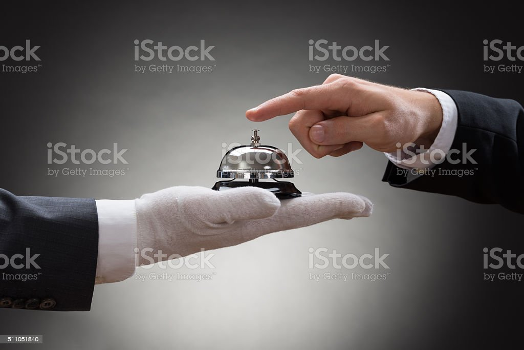 Close-up Of A Person's Hand Ringing Service Bell stock photo