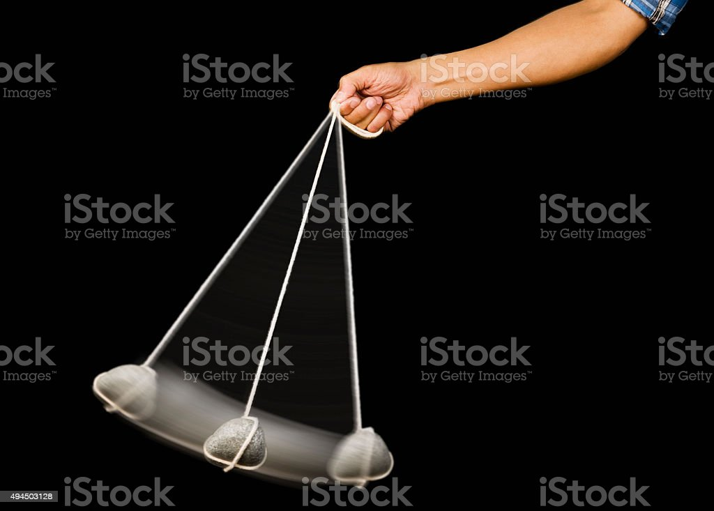Close-up of a person's hand swinging a stone pendulum stock photo