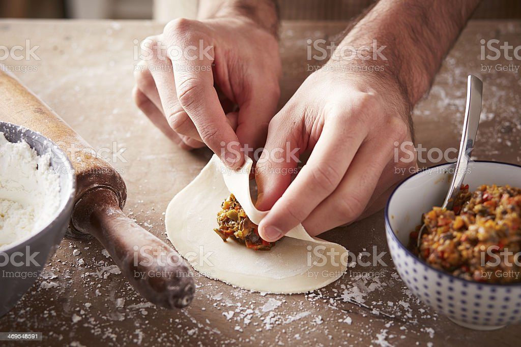 Close-up of a person's hands preparing vegetable dim sums stock photo