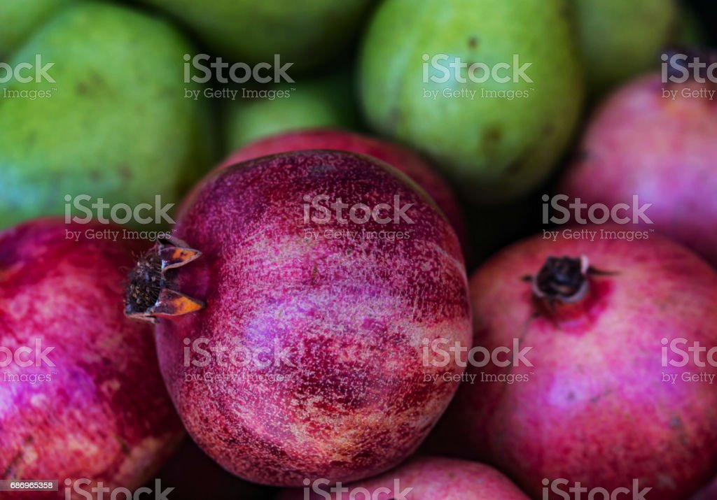 Closeup of a pile of pomegranate, pears in defokus back. stock photo