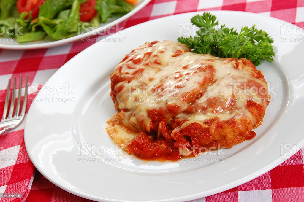 Close-up of a plate of eggplant parmigiana with side salad royalty-free stock photo
