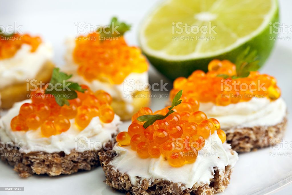 Close-up of a plate of garnished caviar appetizers with lime stock photo