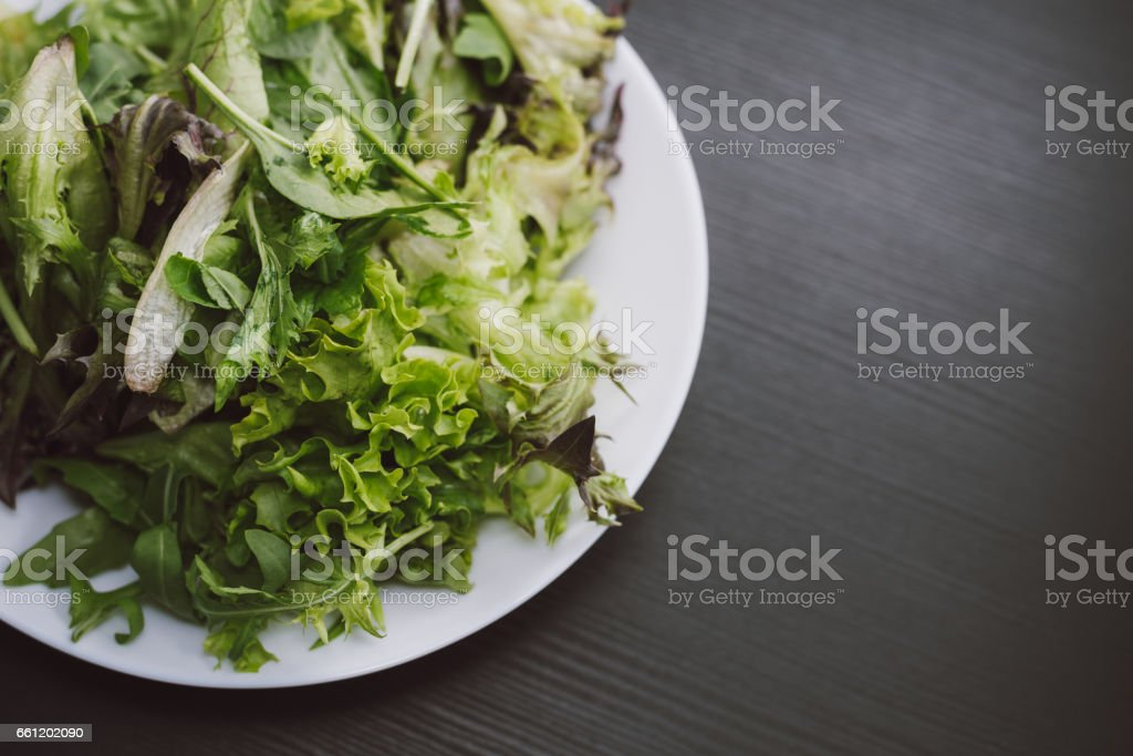 Closeup of a plate of green salad on black texture background. stock photo